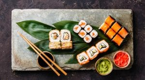 Sushi Set rolls on bamboo green leaf on gray stone slate plate board