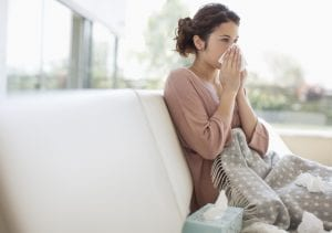 Sick woman blowing her nose in an apartment