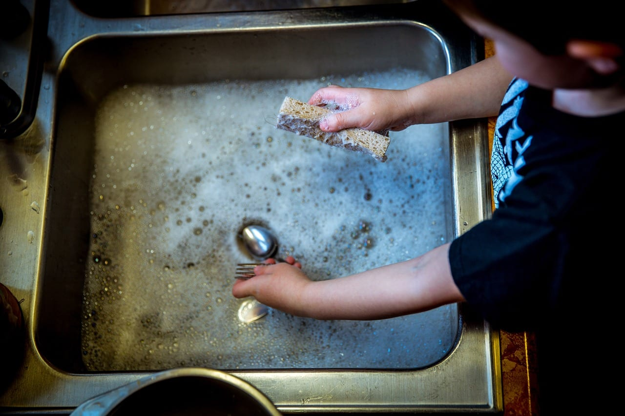 child washes dishes at the kitchen sink
