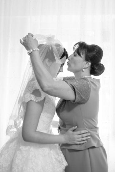 Mother of the bride puts wedding veil on her daughter
