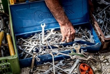Man searching for tools in his toolboxs